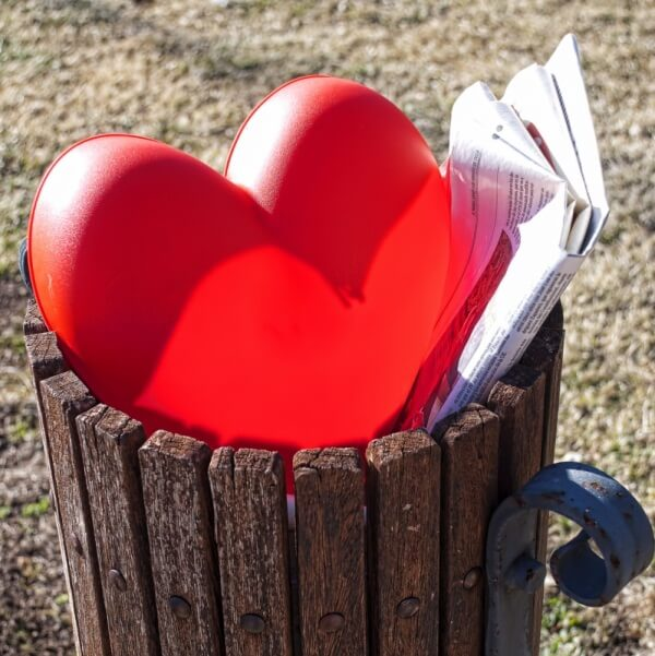 Plastic heart in a trash can