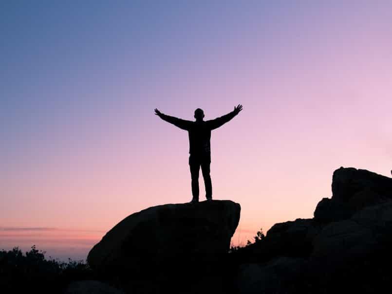 A man standing on rock feeling freedom