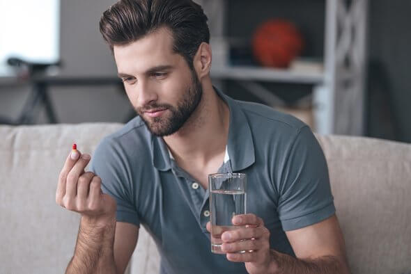 A guy about to take the pill