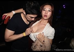 A guy grabbing a drunk girl for her breasts.