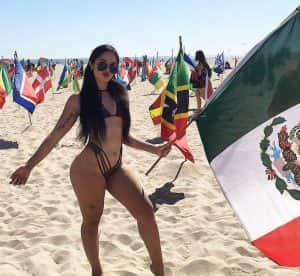 Woman standing on a beach with a Mexican flag