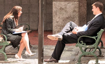 Man and woman talking on a bench.