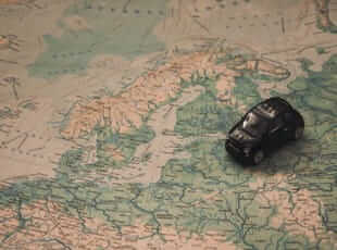 small car on a world map representing travel which is always a good topic to talk about